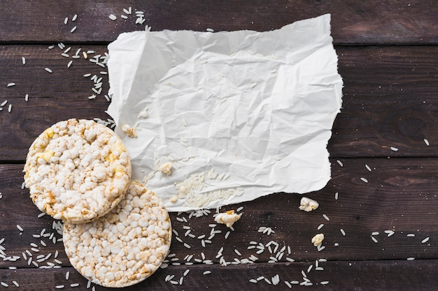 Crumpled paper with two round puffed rice cake with grains on wooden desk Free Photo