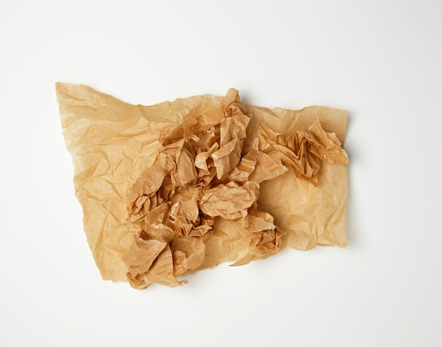 Crumpled piece of brown paper sheet on white Premium Photo