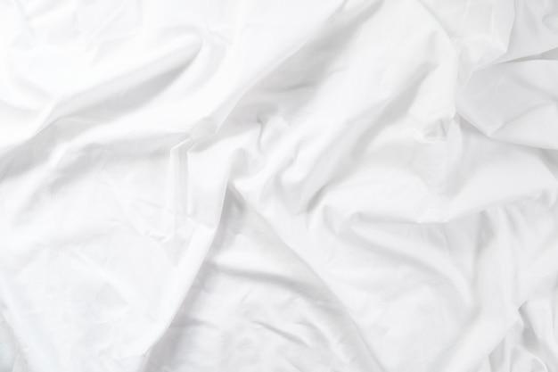 Crumpled sheet. morning bed. white fabric texture. Premium Photo