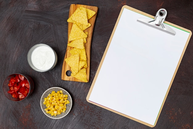 Crunchy nachos vegetables clipboard and white sauces Free Photo