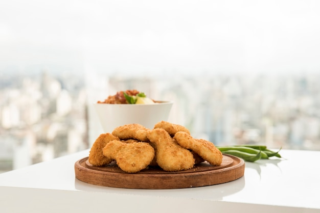 Crusty chicken nuggets served on wooden plate Free Photo