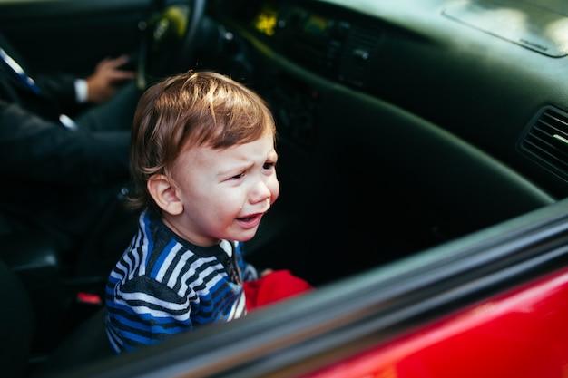 Crying baby boy in car. Premium Photo
