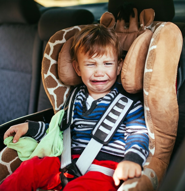 Crying baby boy in a safety car seat Premium Photo