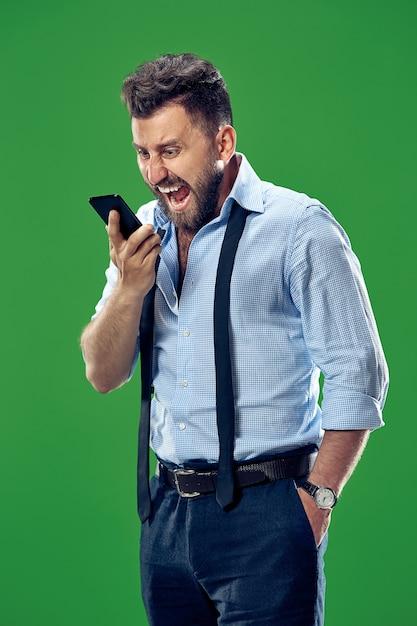 緑のスタジオで叫んでいる携帯電話で泣いている感情的な怒っている人。 無料写真