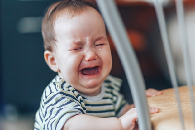 Crying little cutie drk-haired girl, stands crying loudly, standing near chair at home Premium Photo