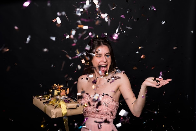 Crying woman with present boxes between confetti Free Photo
