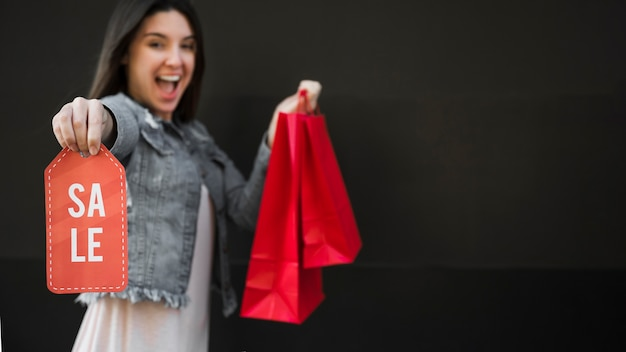 Crying woman with shopping packets and sale tablet Free Photo