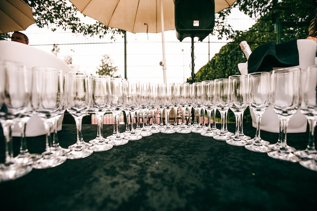 Crystal champagne flutes stand on a table Free Photo