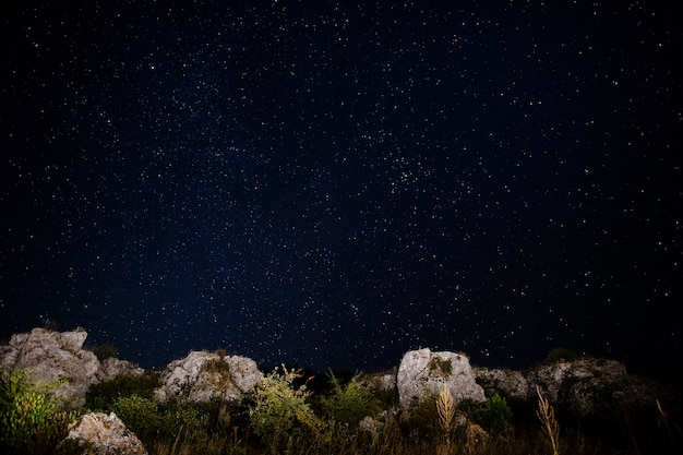 Crystal clear sky with stars and rocks on the ground Free Photo