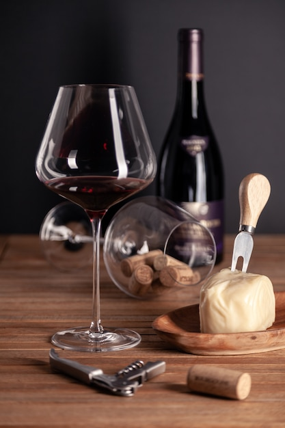 Crystal glass of red wine, bottles, corkscrew, decanter, cheese, corks on wooden table Premium Photo