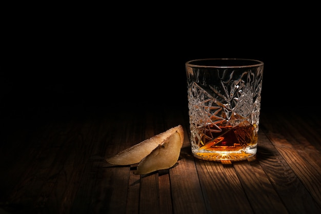 Crystal glass of whiskey on a wooden table on black Premium Photo