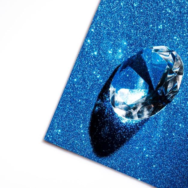 Crystal transparent diamond on blue shimmer sparkling backdrop Free Photo