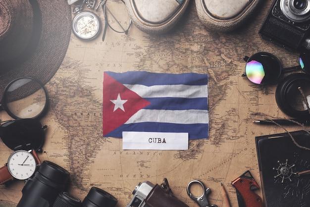 Cuba flag between traveler's accessories on old vintage map. overhead shot Premium Photo