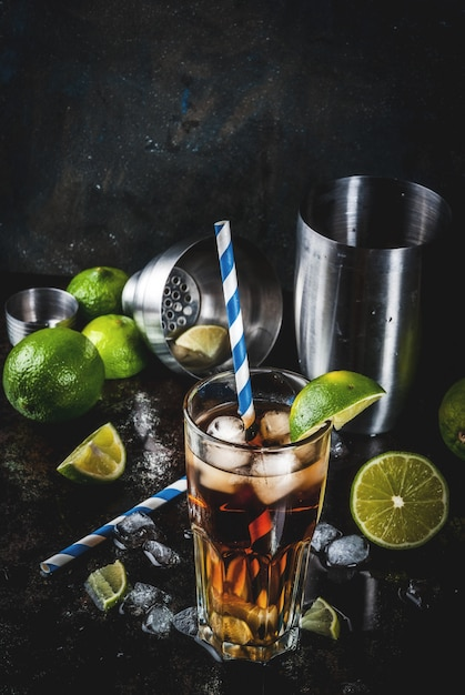 Cuba libre, long island or iced tea cocktail with strong alcohol, cola, lime and ice, two glass, dark  copyspace Premium Photo