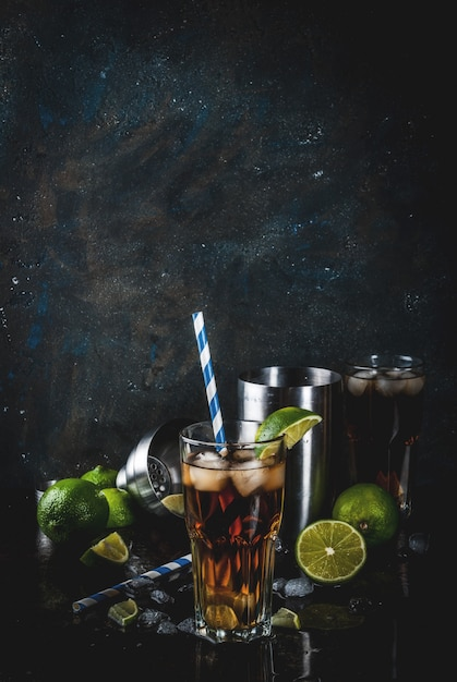 Cuba libre, long island or iced tea cocktail with strong alcohol, cola, lime and ice, two glass, dark surface copy space Premium Photo