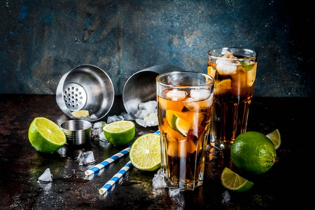Cuba libre, long island or iced tea cocktail with strong alcohol, cola, lime and ice, two glass Premium Photo
