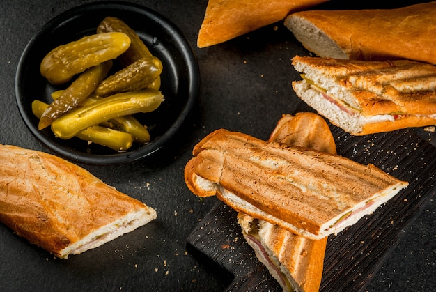 Cuban traditional food, snack, party food. cuban sandwich from baguette with ham, pork, cheese, pickles. on black table copyspace Premium Photo