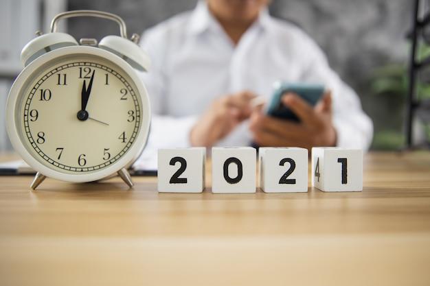 オンラインで働く電話を使用してビジネスマンと木製のテーブルの年番号2021のキューブ Premium写真