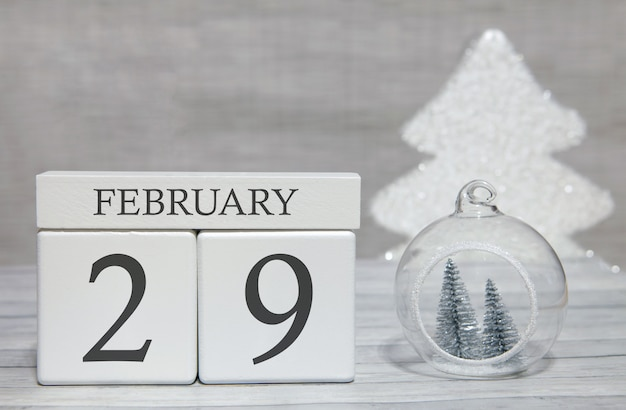 Cube shape calendar for february 29 on wooden surface and light background Premium Photo
