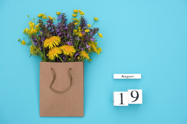 Cubes calendar august 19 and field colorful rustic flowers in craft package on blue background Premium Photo
