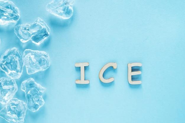 青色の背景に氷のキューブ。木製の文字で書かれた氷の単語。上面図 Premium写真
