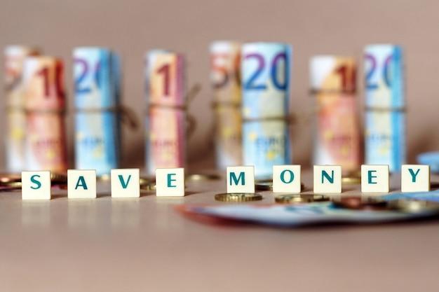 Кубики с надписью «сэкономьте деньги» на столе с купюрами и монетами в испанских динеро Бесплатные Фотографии