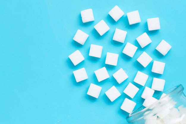 Cubes of sugar on a blue background. Premium Photo