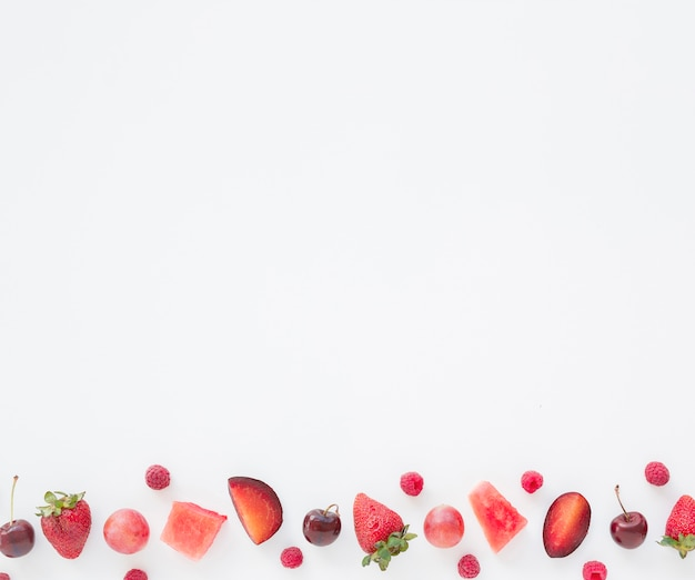 Cubes watermelon; raspberries; plum; cherries and strawberries on the side of white background Free Photo