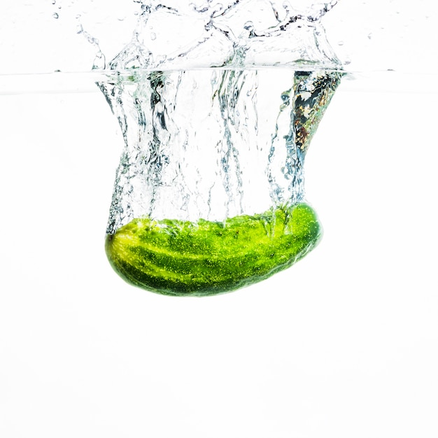 Cucumber falling in water with water splash against white background Free Photo