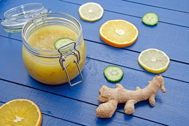 Варенье из огурцов в стеклянной банке с кусочками ингредиентов апельсина, лимона, огурца и имбиря на синем деревянном столе Premium Фотографии