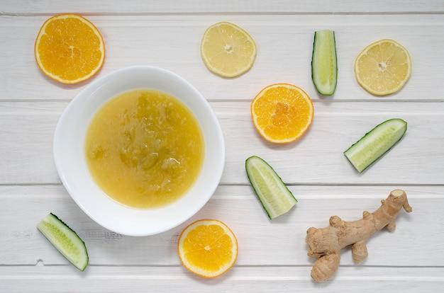 Варенье из огурцов с дольками апельсина, лимона и имбиря на светлом деревянном столе. концепция здорового питания. Premium Фотографии
