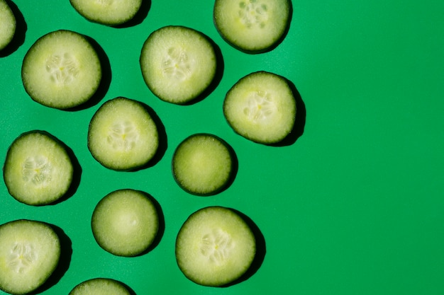 Cucumber slices arranged on green background Free Photo