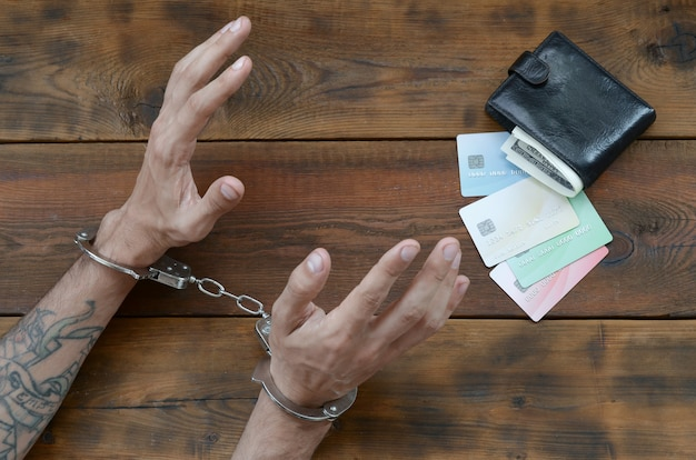 Cuffed hands of tattooed criminal suspect of carding and fake credit cards Premium Photo