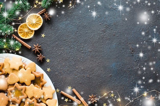 Culinary background with freshly baked christmas gingerbread, spices and fir branches. copy space. Premium Photo