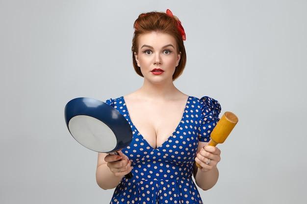 Culinario e cucina. stupita bella giovane casalinga caucasica che indossa un abito punteggiato vintage con taglio basso fissando la telecamera con la bocca aperta, tenendo la padella e il mattarello Foto Gratuite