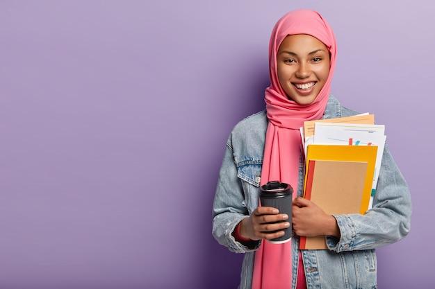 Культура, религия и концепция изучения. радостная мусульманка с зубастой улыбкой несет блокнот с бумагами, кофе на вынос Бесплатные Фотографии