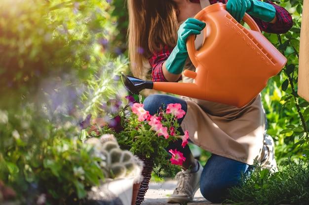 家の庭の花に水をまく庭師女性。ガーデニングと花culture栽培、フラワーケア Premium写真