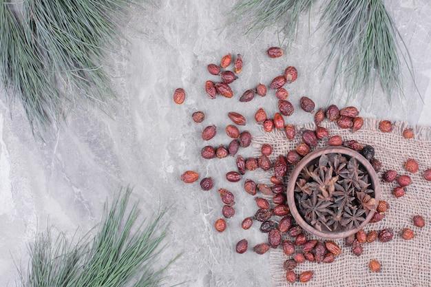 Una tazza di fiori di anice con i fianchi asciutti intorno. Foto Gratuite