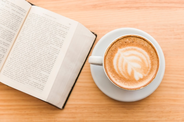 Cup of art latte on a cappuccino coffee and open book on table Free Photo