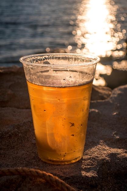 Tazza di birra sullo sfondo dell'oceano durante il tramonto Foto Gratuite