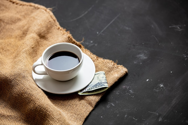 Cup of black coffee and payment on the table Premium Photo