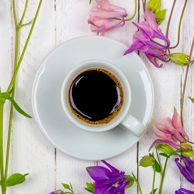 A cup of black coffee on a saucer and flowers on a white table Premium Photo