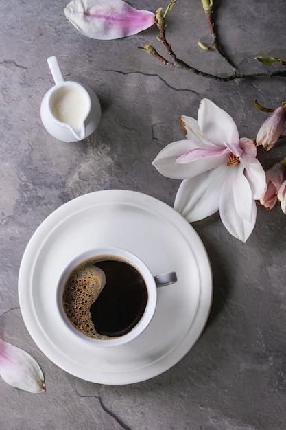 Cup of black coffee with magnolia Premium Photo