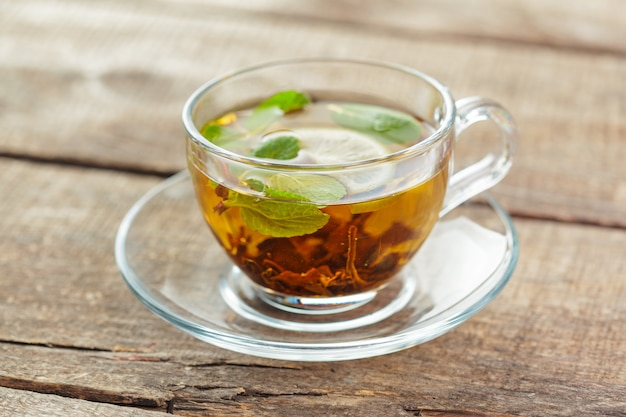 Cup of black tea with mint leaves on a wooden table Premium Photo