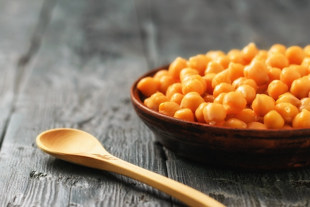 A cup of boiled chickpeas with a wooden spoon on a black wooden table. vegetarian cuisine from legumes. Premium Photo