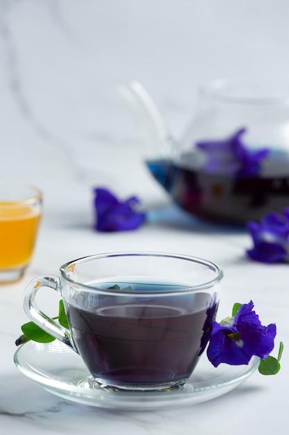 Tazza di tè ai fiori di pisello farfalla con miele sul tavolo Foto Gratuite