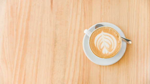 Cup of cappuccino coffee with art latte and spoon on wooden background Free Photo