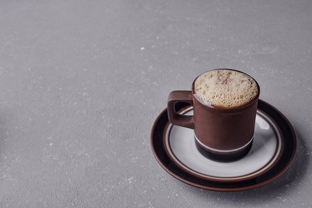 A cup of cappuccino on grey background. Free Photo