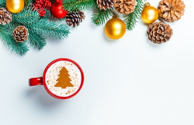 Cup of cappuccino with christmas tree shape on a white table. Premium Photo
