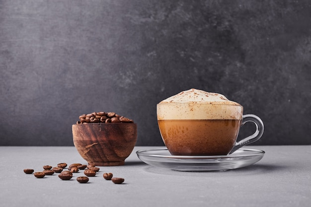 A cup of cappuccino with coffee beans around. Free Photo